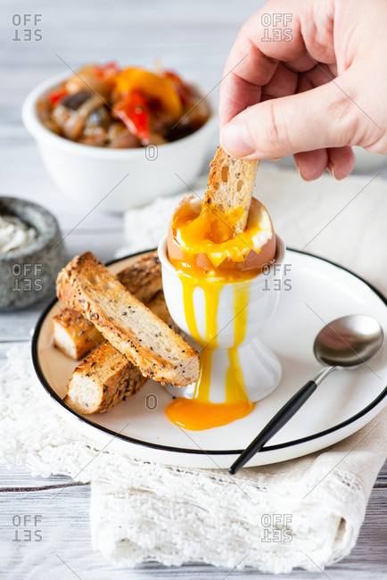 Person dipping bread into soft egg yolk