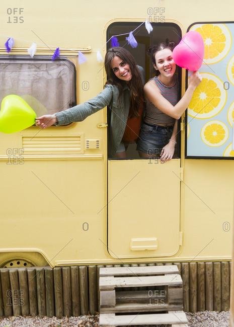 Best friends girls enjoying in a caravan holding heart balloons