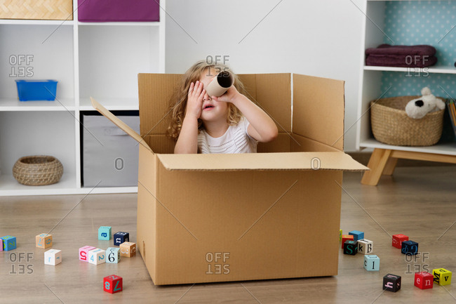 Playful girl looking through cardboard tube while sitting in box