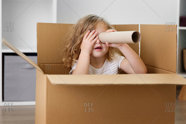 Young girl looking through cardboard tube while sitting in box