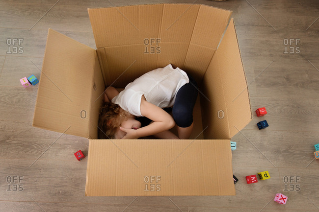 Playful young child hiding in cardboard box