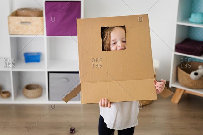 Playful little girl wearing cardboard box on head