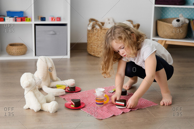 Little girl having tea party with stuffed toys at home