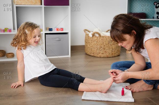 Mother applying nail polish to daughter's toenails