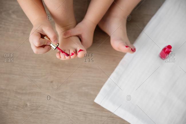 Close up of little girl applying nail polish to toenails
