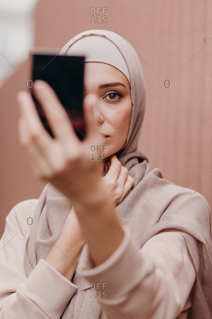 Muslim girl looks in the mirror and adjusts her hijab.
