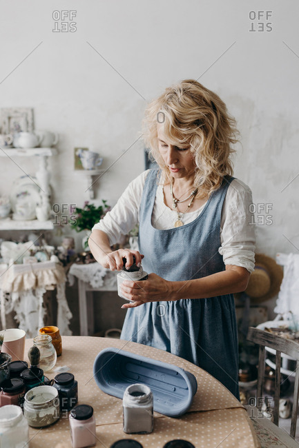 Female artist mixes a paint for painting a vase.