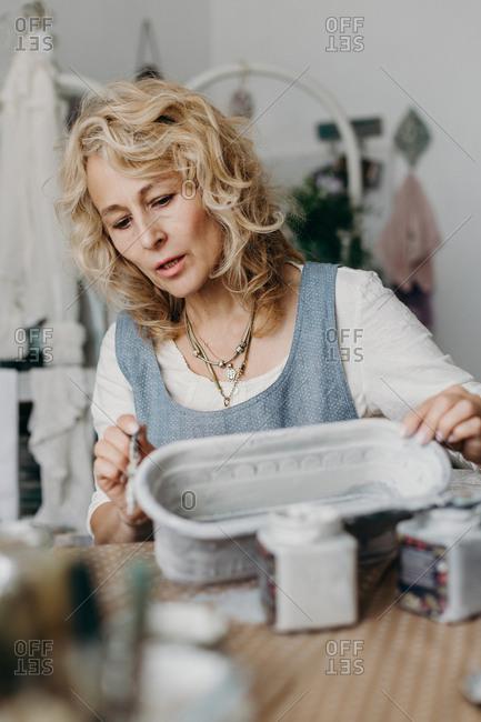 A female artist paints a flower pot in a cozy studio.