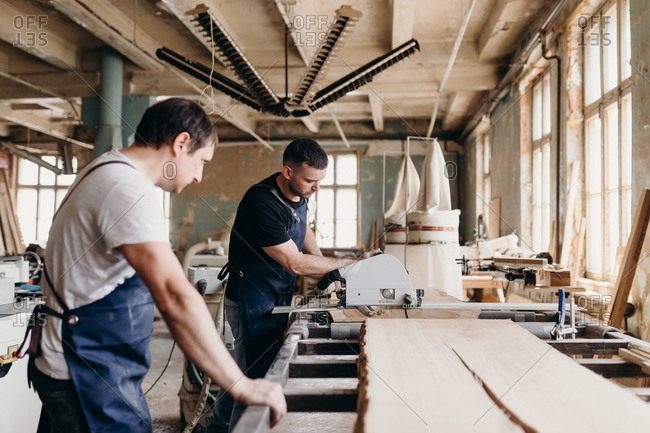 Two colleagues do cutting of big piece of wood by special machine.