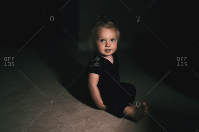 Cute baby girl sitting in low light