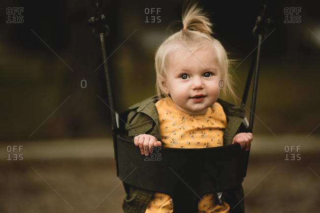 Adorable baby girl in a baby swing at a park