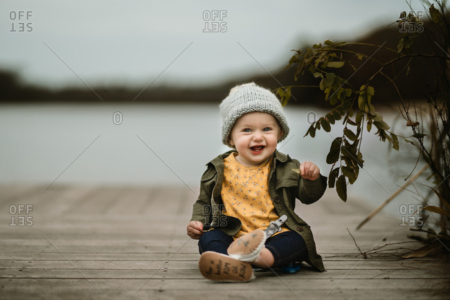 Adorable baby girl sitting on a wooden dock