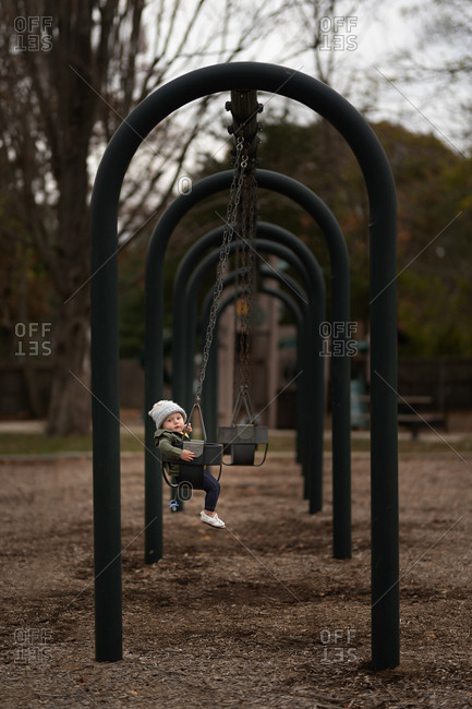 Baby girl in a baby swing at a park