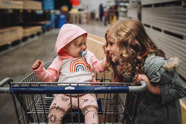 Girl looking at baby sister in a shopping cart