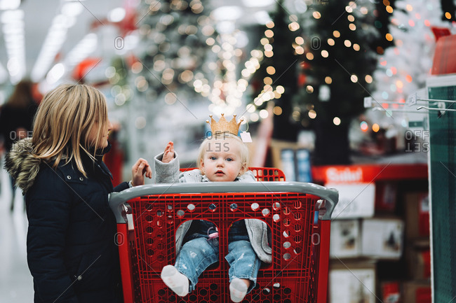 Girl standing by shopping cart with her baby sister in it and wearing a crown