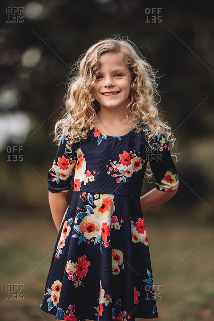 Blonde girl with curly hair wearing a floral dress