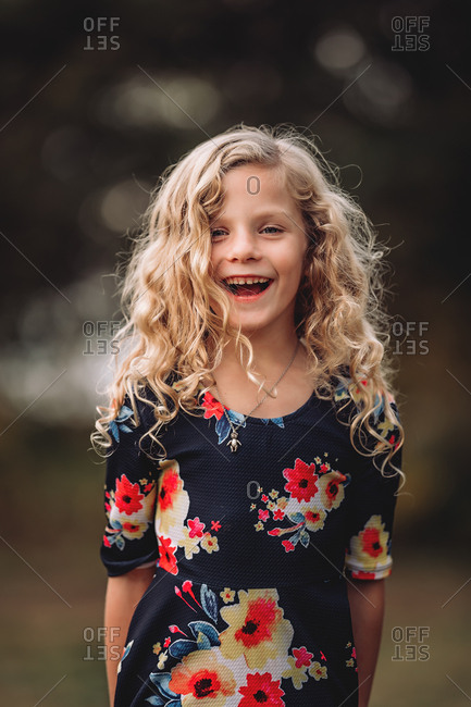 Happy blonde girl with curly hair wearing a floral dress