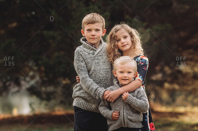 Portrait of three young kids outdoors