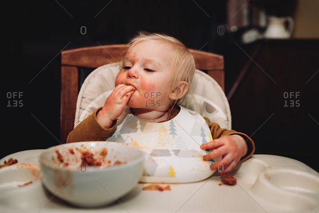Blonde baby eating food in a highchair