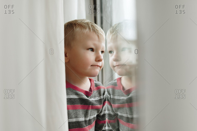 Little blonde boy looking out window with reflection
