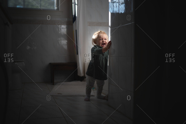 Blonde baby girl standing in bathroom screaming
