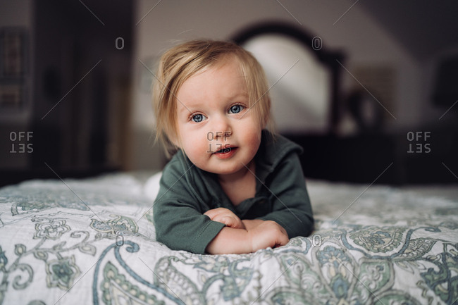 Blonde baby girl lying on bed