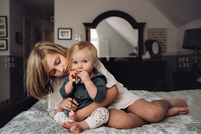 Girl and her baby sister on bed