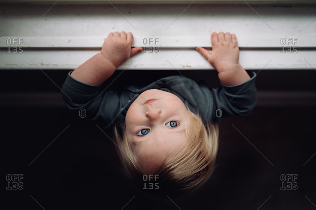 Overhead view of blond haired baby hanging on windowsill