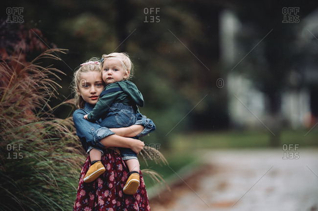 Young blonde girl carrying her baby sister