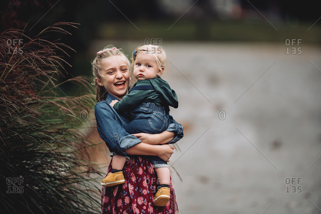 Blonde girl carrying her baby sister and laughing