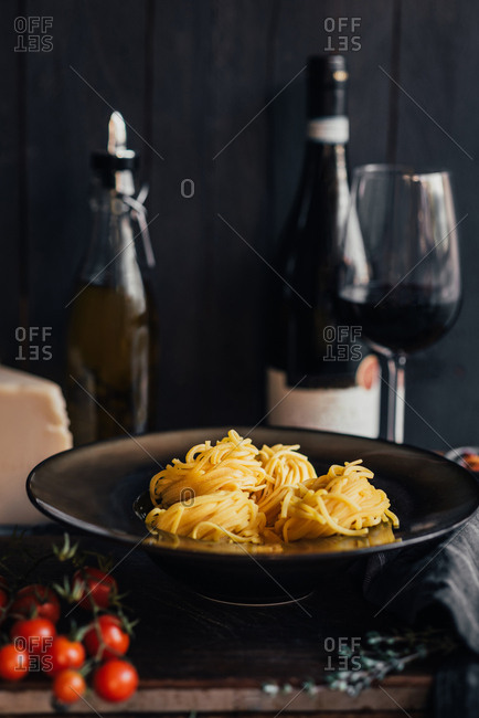 Homemade pasta on a plate next to a bottle of red wine