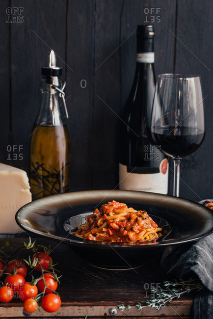 Homemade pasta with tomato sauce in a plate next to a bottle of red wine