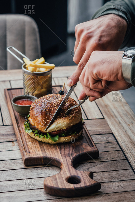 Man eating a beef burger with fries