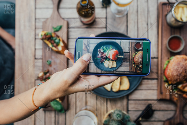 Person taking a photo of food on a table with a mobile phone
