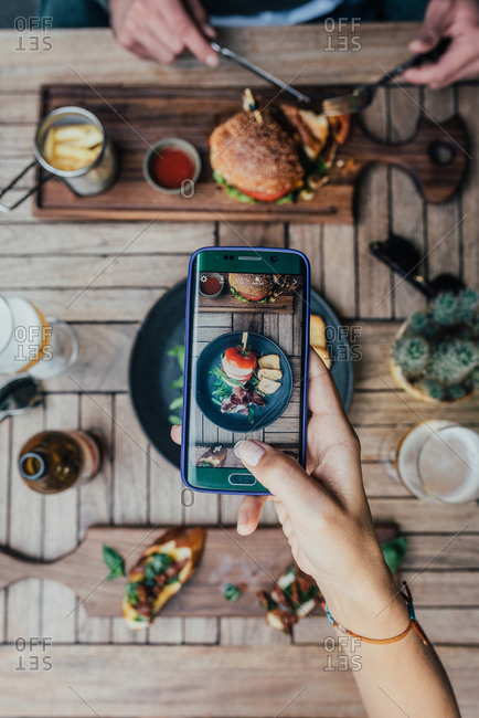 Woman taking a photo of food on a table with a mobile phone
