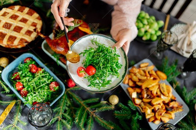Woman putting salad on a plate during a holiday dinner