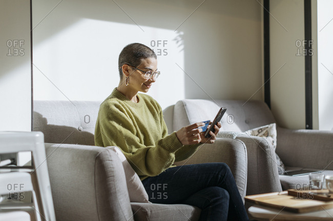 Woman with short hair sitting in a comfy chair in a cafe cell phone