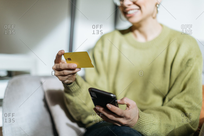 Close up of a woman using phone to make credit card payment