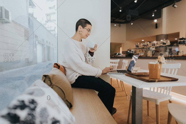 Woman with short hair drinking coffee in a cafe while using laptop