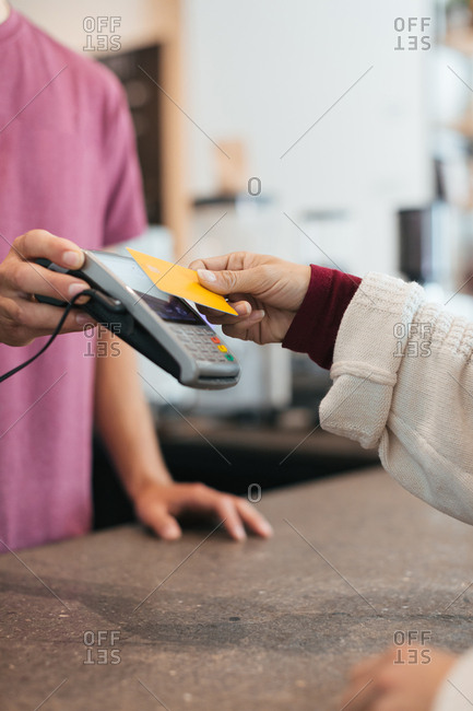 Woman paying for coffee with the tap to pay option of her credit card