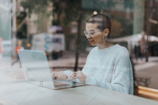View through window of cafe of a woman with short hair working on her laptop