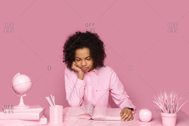 Conceptual portrait of fashionable black girl with afro hair style sitting at table and looking at blank pink album pages with interest on pink wall background
