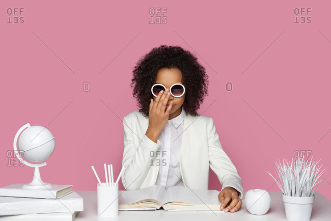 Portrait of fashionable African-American girl in white shirt and jacket settling round sunglasses while sitting at table in front of blank album on pink wall background