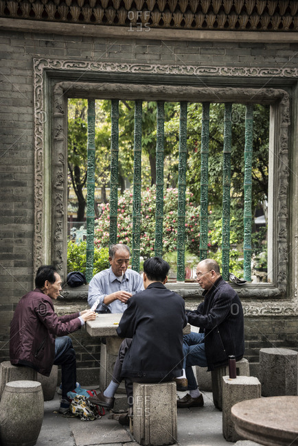 Foshan, China - February 22, 2017: Chinese men playing cards in Zumiao ancestral temple, Foshan