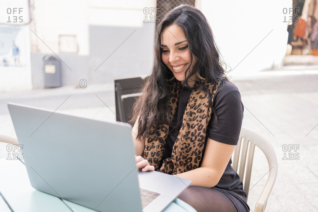 Cute young lady smiling and browsing modern laptop while sitting at table