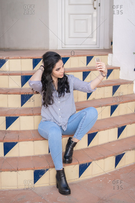 Young woman taking selfie with mobile phone while sitting on stairs