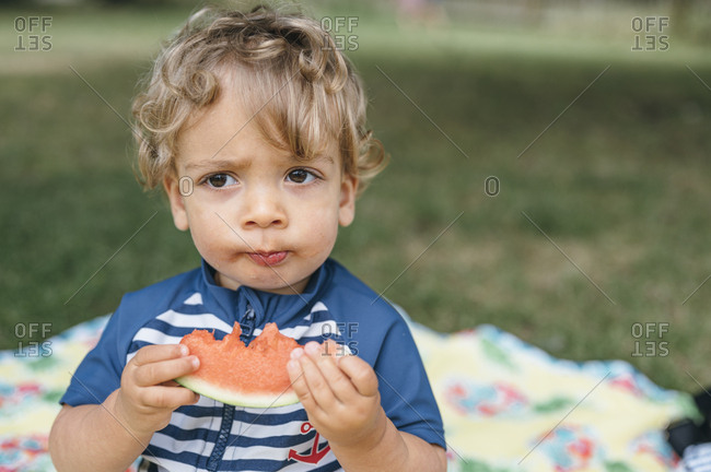 Young boy in bathsuit eats watermelon on the grass