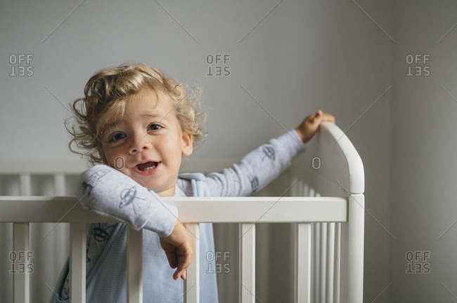 Curly hair Baby boy smiling in his cot