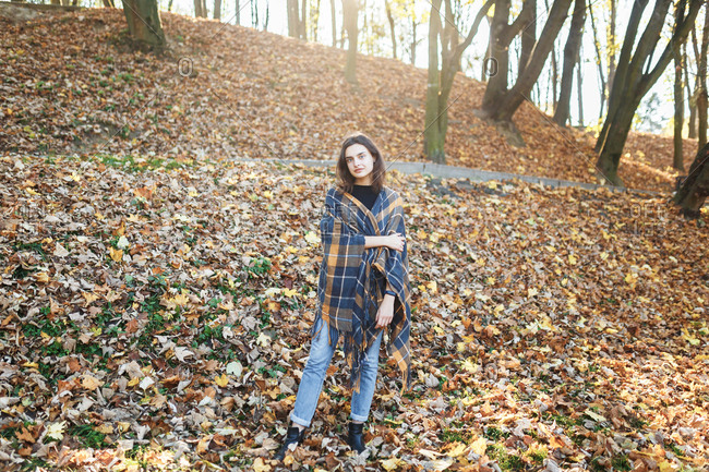 Woman standing in the woods with leaves falling