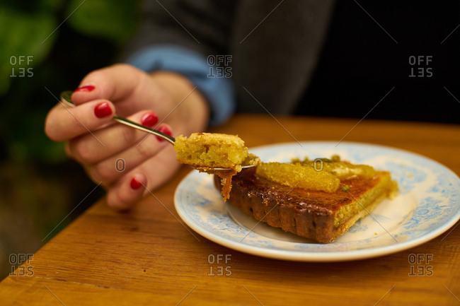 Female hand holding a spoon eating a dessert in a cafe